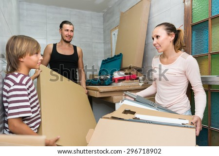 Positive friendly family of three packing things before relocation