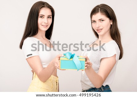 Positive friends portrait of two happy girls with present, funny faces, grimaces, joy, emotions, casual style on light grey background