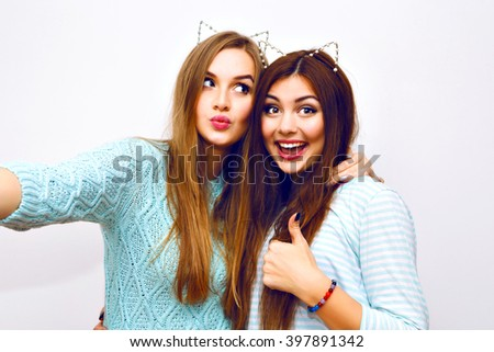 Positive friends portrait of two happy sister girls making selfie, sure funny faces, grimaces,joy, emotions, casual style, pastel colors, white wall. Sending air kiss, and say ok. - stock photo