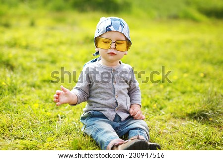Positive funny little child in sunglasses on the grass summer - stock photo
