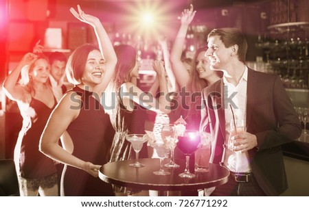 Positive glad colleagues dancing on corporate party with cocktails in hands
