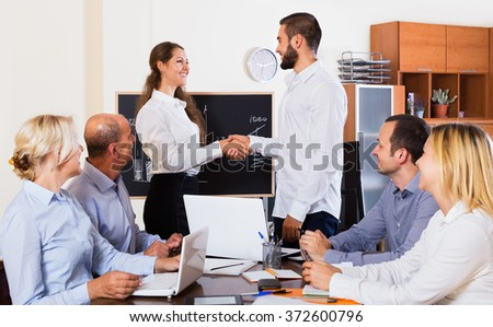 Positive happy colleagues discussing a price development at the office  - stock photo