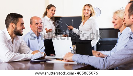 Positive happy colleagues discussing price development in the office  - stock photo