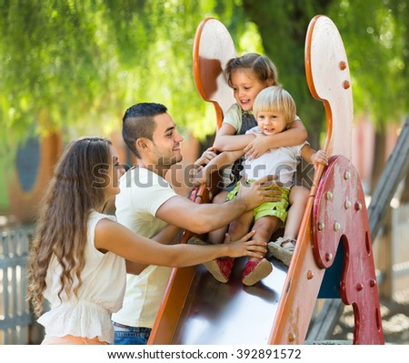Positive happy family of four at children's playground. Focus on girl - stock photo