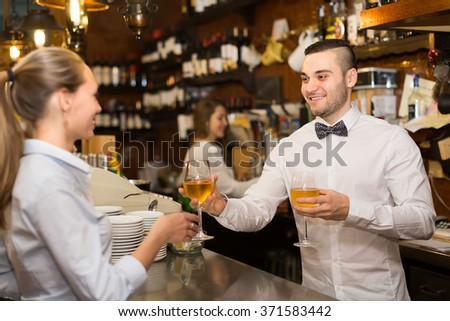 Positive happy female drinking wine at counter and chatting with bartenders