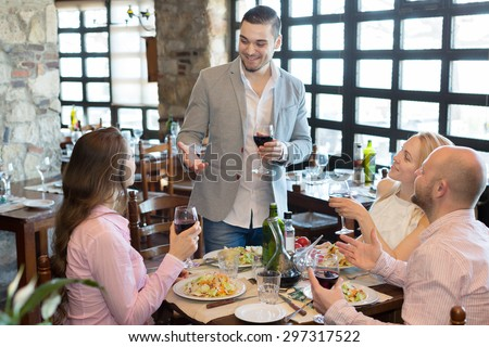 Positive happy young people enjoying a food and smiling in tavern  - stock photo