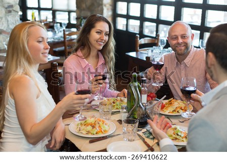 Positive happy young people enjoying food and smiling at tavern  - stock photo