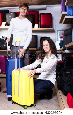 Positive husband and young wife selecting handy trunk in store. Focus on the woman