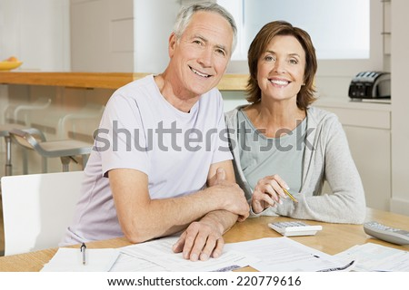 Positive image of mature heterosexual couple looking to camera while doing paperwork in domestic setting - stock photo