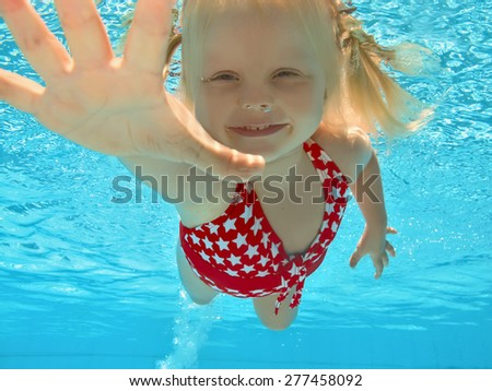 Positive little baby with smile and open eyes diving underwater with fun in the clear blue water. Healthy lifestyle and child swimming during summer family vacation in the tropical resort pool - stock photo