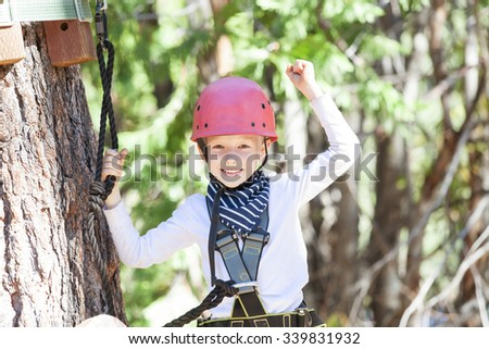positive little boy feeling happy after climbing at treetop adventure park - stock photo