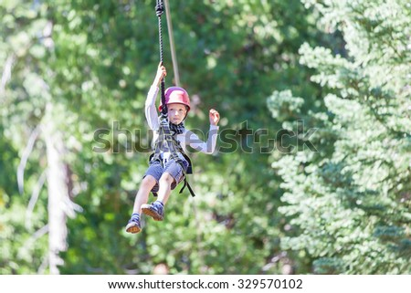 positive little boy ziplining at outdoor treetop adventure park being active and brave - stock photo
