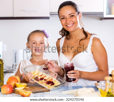 Positive little daughter helping mom to make apple cake at home. Focus on the girl