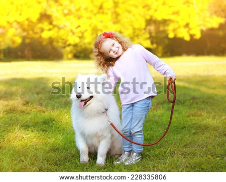 Positive little girl and dog having fun outdoors in warm sunny day - stock photo