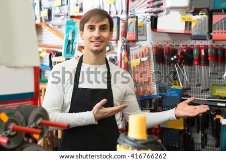 positive male seller posing at tooling section of household store