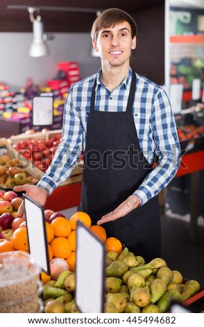 positive  male seller posing with apples, tangerines and bananas in store