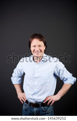 Positive man standing with his hands on his hips and a delightful smile full of optimism on a dark background - stock photo
