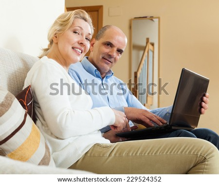 Positive mature couple  with laptop in room at home