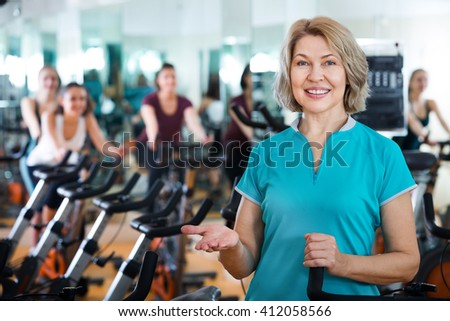 Positive mature woman posing in modern gym for females