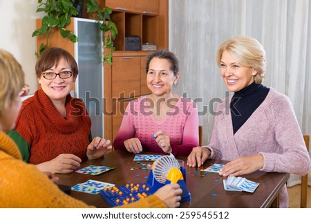 Positive mature women having fun with table game indoor  - stock photo