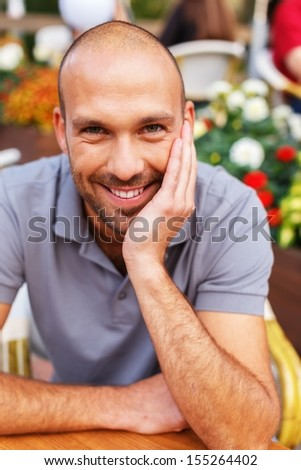 Positive middle-aged man alone behind table in summer cafe - stock photo