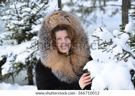 Positive middle-aged woman in a fur coat in the winter park