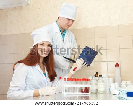Positive nurse and male doctor works with test tubes in clinic lab  - stock photo
