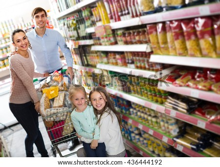 Positive parents with two girls and purchases in shopping cart