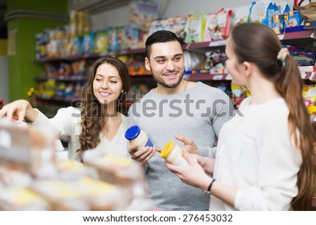 Positive people choosing tinned food at supermarket - stock photo