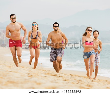 Positive people running together at ocean beach in summer day