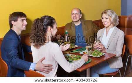 Positive pleasant cheerful middle class people enjoying food and wine in cafe