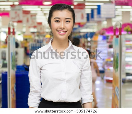 Positive sales assistant portrait in supermarket store in Asia.