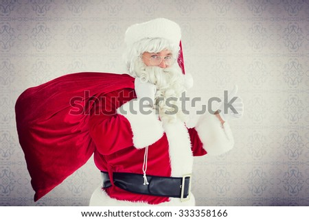 Positive santa with his sack and thumbs up against room with wooden floor - stock photo