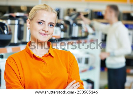 Positive seller or shop assistant portrait  in supermarket store - stock photo