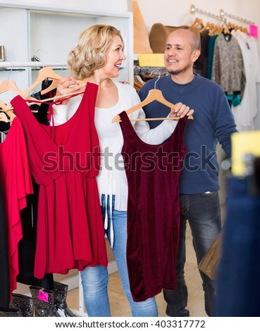 Positive senior husband helping wife to select dress at apparel store