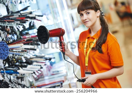Positive shop assistant in home electric appliance supermarket store - stock photo