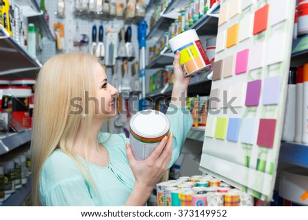 Positive smiling blonde girl choosing exterior decorating paint in shopping mall - stock photo