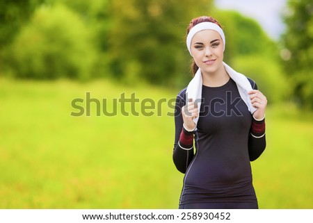 Positive Smiling Caucasian Fit Woman With Towel on Neck Standing Outdoors Prior to Her Jogging Exercises. Horizontal Image - stock photo