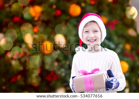 positive smiling child in santa's hat and warm winter clothes holding christmas gift enjoying christmas time by the tree