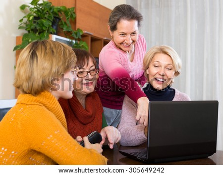 Positive smiling elderly female friends browsing web on laptop at home