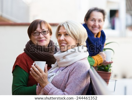 Positive smiling elderly female friends drinking coffee at patio. Focus on blonde  - stock photo