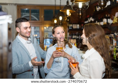 Positive smiling girls flirting with man at bar of restaurant  - stock photo
