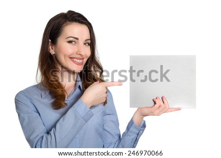 Positive smiling woman  in blue shirt pointing at blank piece of paper copy space isolated on white background - stock photo