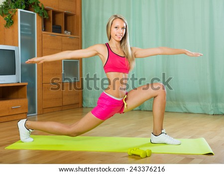 Positive smiling young woman working out with dumbbells at home  - stock photo