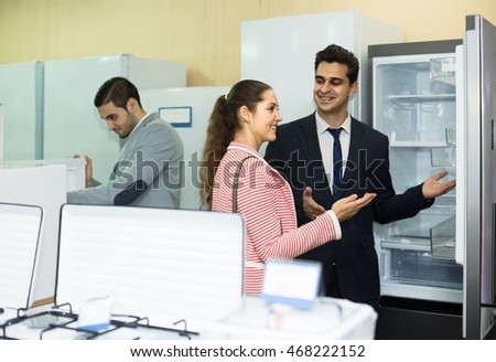 positive spanish couple choosing new refrigerator in hypermarket and smiling