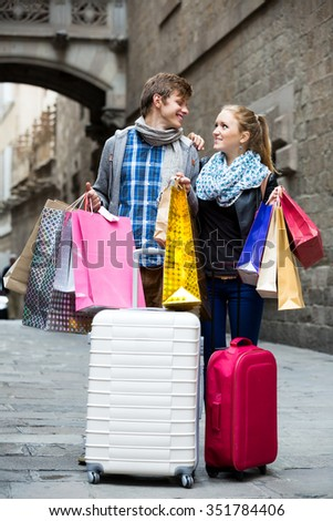 Positive spouse walking through European town and carrying shopping bags