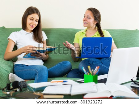 Positive teenage student girls studying at home with books and computers - stock photo