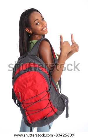 Positive thumbs up success for pretty young African American teenager school girl, with long black hair wearing green t-shirt and red school backpack with beautiful smile. - stock photo