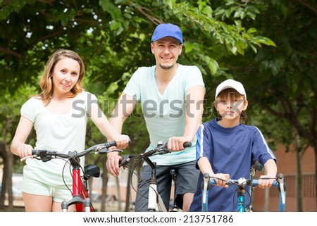 Positive tourists with son riding bicycles in park in sunny day
