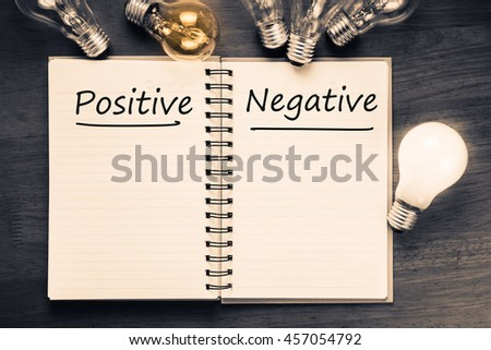 Positive Versus Negative on notebook with glowing light bulbs
